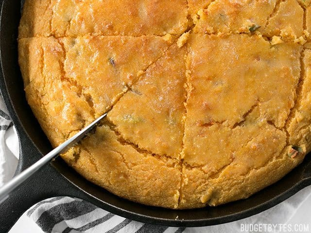 Close up of slicing Hatch Chile Sweet Potato Cornbread in skillet