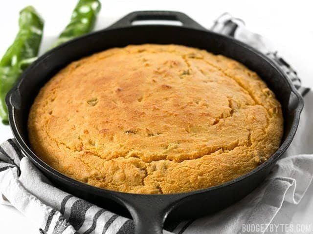 Side view of Hatch Chile Sweet Potato Cornbread in cast iron skillet sitting on napkin with two chilis in the background