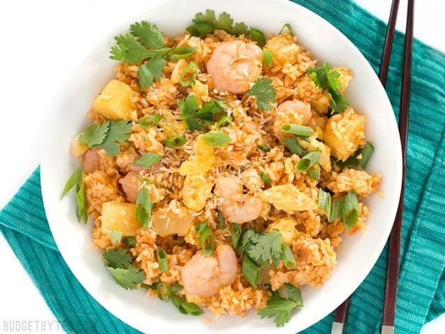 Overhead view of a bowl of Shrimp Fried Rice with Pineapple and Toasted Coconut on a teal napkin