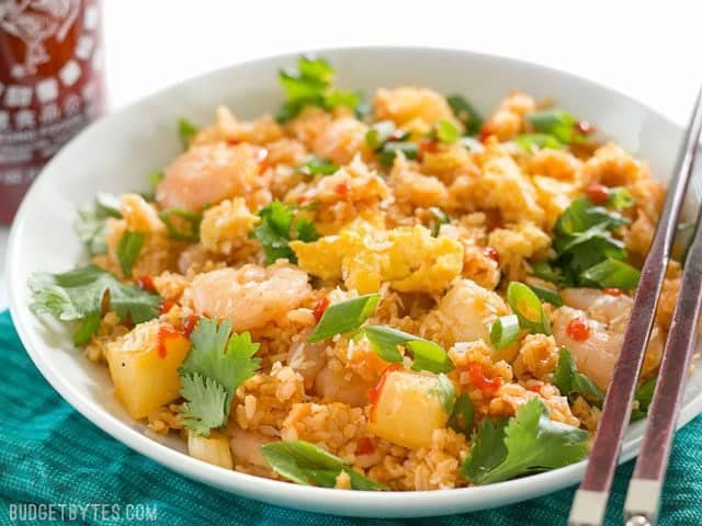 Front view of a bowl of Shrimp Fried Rice with Pineapple and Toasted Coconut with a bottle of sriracha in the back.