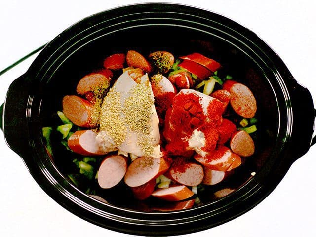 Sliced Sausage, Chicken Thighs and Spices added to slow cooker