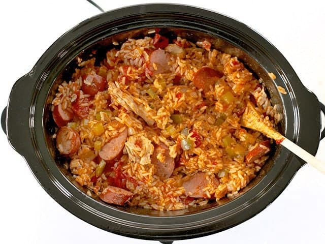 Stirring dish with wooden spoon in slow cooker