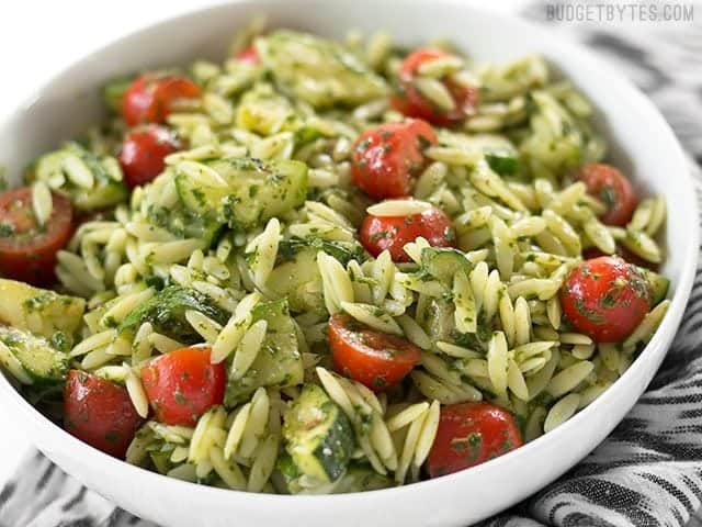 Side view of a bowl full of Zucchini and Orzo Salad with Chimichurri