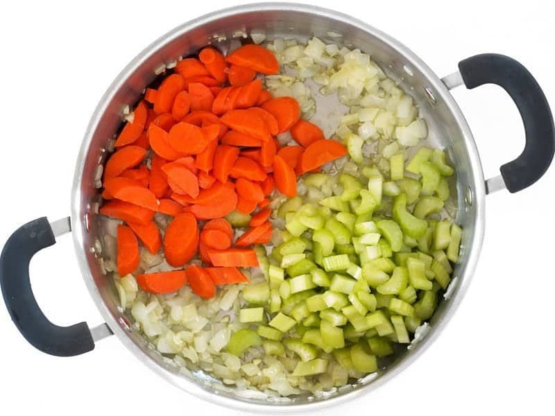 Carrots and celery added to the pot with onion and garlic
