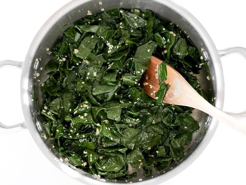 Sautéed kale in a pot with soy sauce and sesame seeds