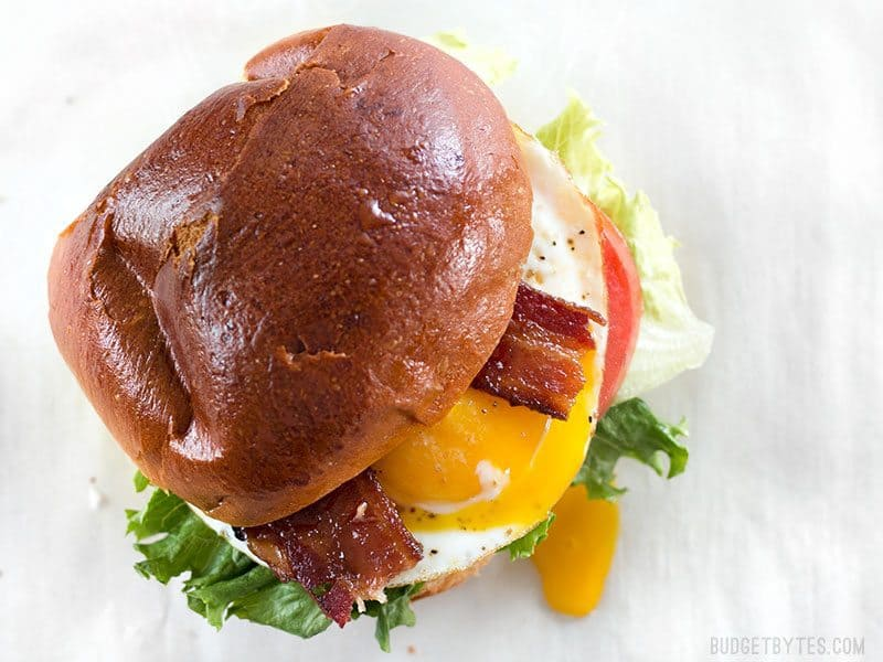 Overhead view of a Brown Sugar Bacon Breakfast Sandwiches with the yolk dripping down the side