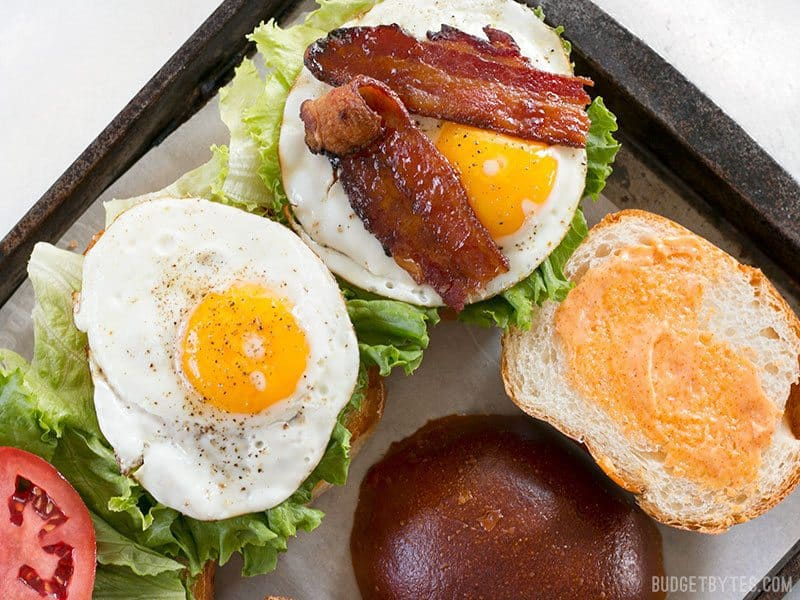 Brown Sugar Bacon Breakfast Sandwiches on a baking sheet being assembled