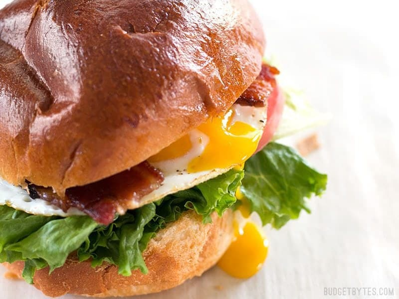 Close up of a runny yolk dripping down the side of a Brown Sugar Bacon Breakfast Sandwiches