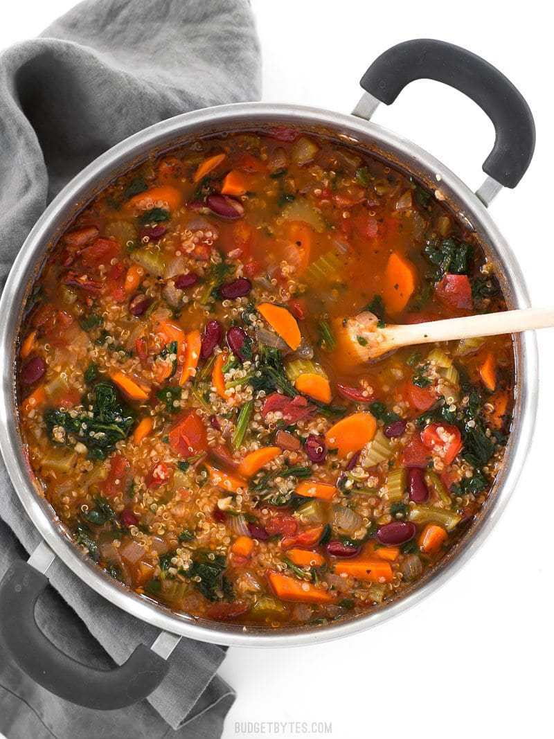 Overhead view of a pot full of Garden Vegetable Quinoa Soup with a wooden spoon stuck in the middle