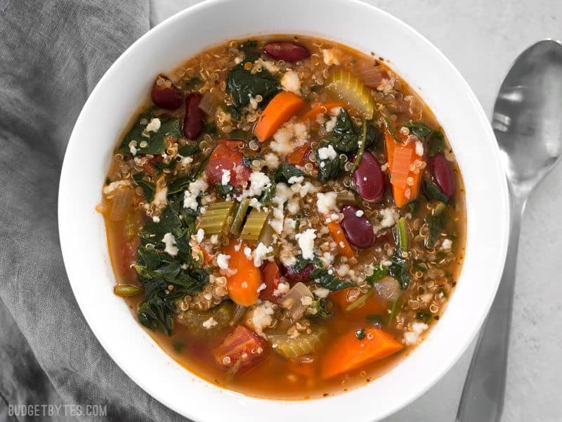 A bowl full of Garden Vegetable Quinoa Soup topped with a little crumbled queso fresco
