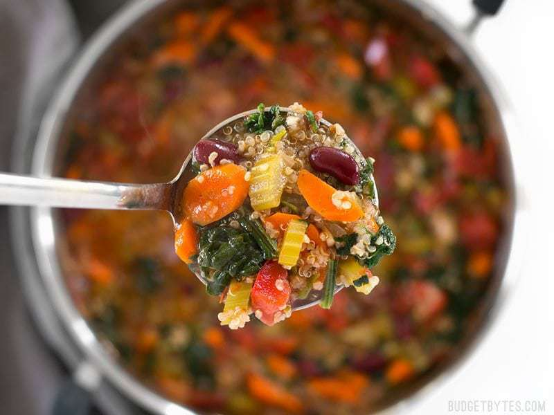Close up of a ladle full of Garden Vegetable Quinoa Soup with the pot in the background