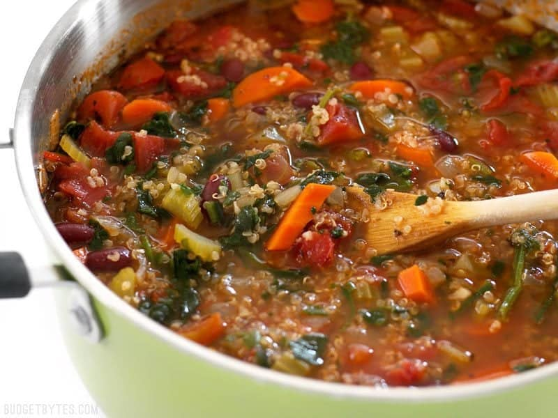 Close up side view of the pot of Garden Vegetable Quinoa Soup with a wooden spoon lifting some of the vegetables