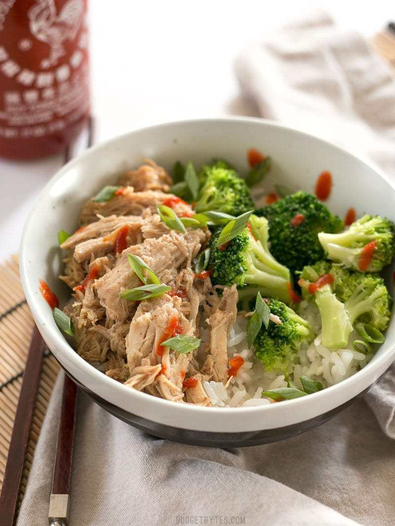 Front view of 5 Spice Pulled Pork in a bowl with rice, broccoli, green onion, and a drizzle of sriracha.