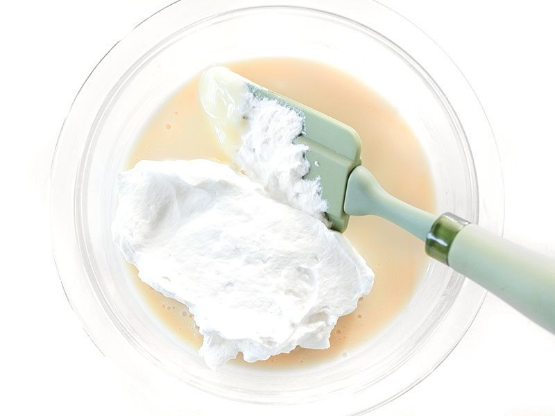 Whipped Cream beginning to be folded into sweetened condensed milk