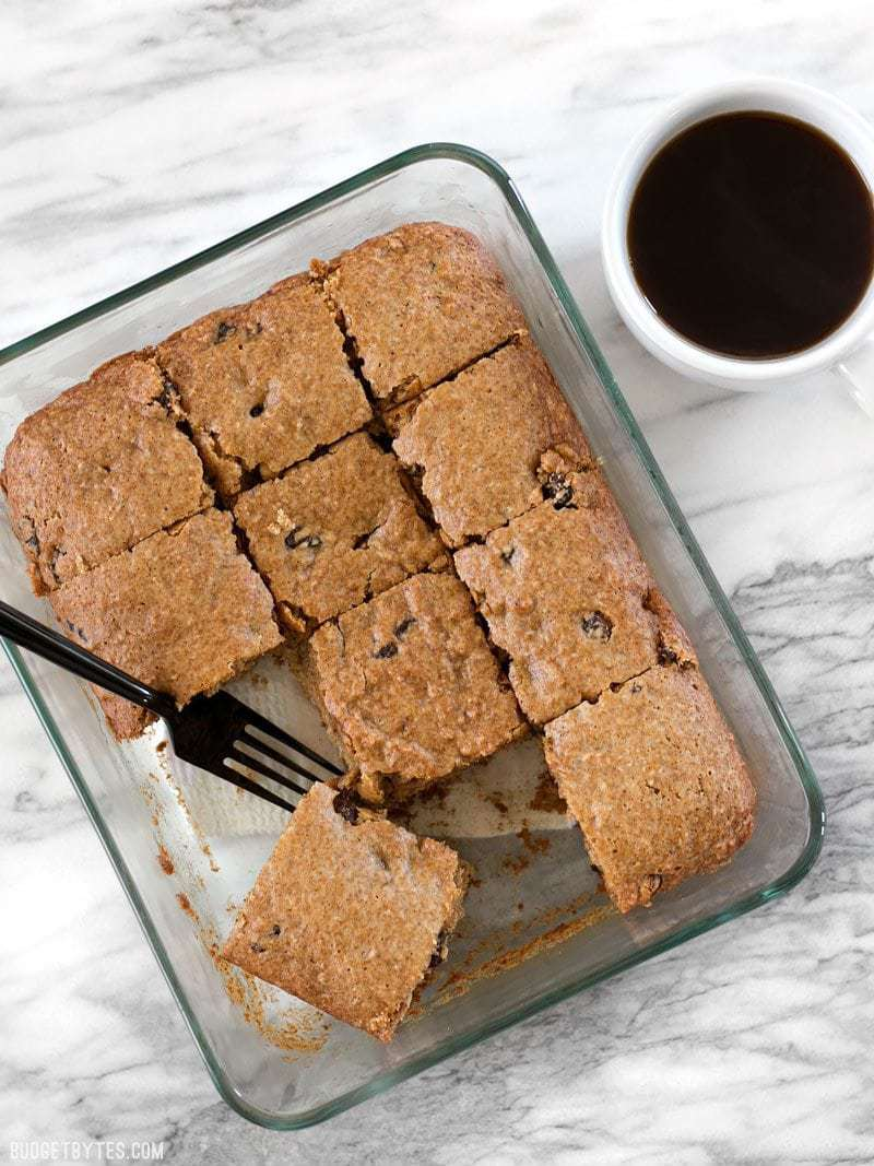 A class casserole dish with baked Applesauce Cake, a fork resting in the dish, a cup of coffee on the side.