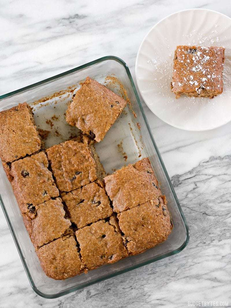 Applesauce Cake cut into squares, one square on a small plate o the side, dusted with powdered sugar