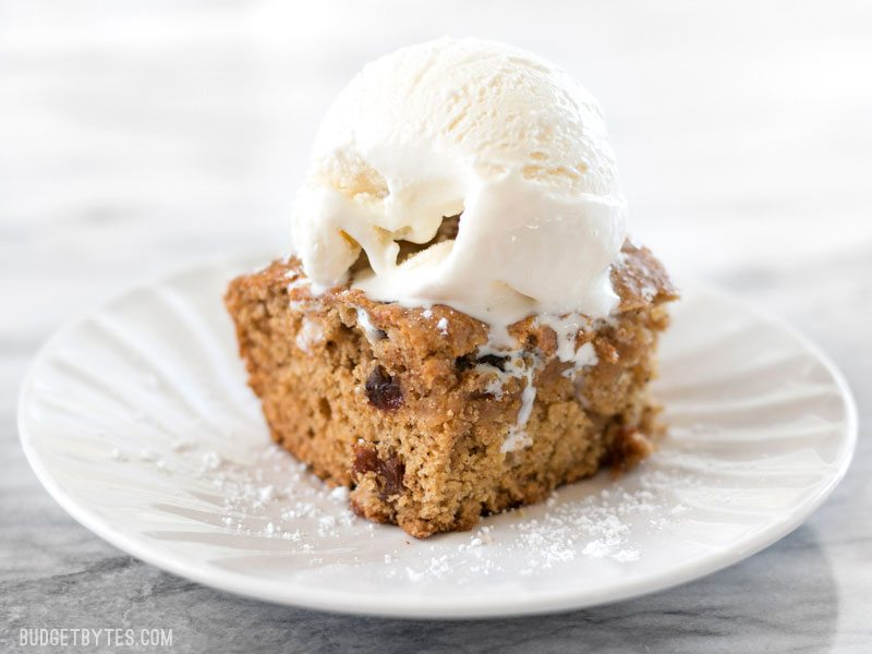 Close up of one square of Applesauce Cake with a scoop of vanilla ice cream on top.