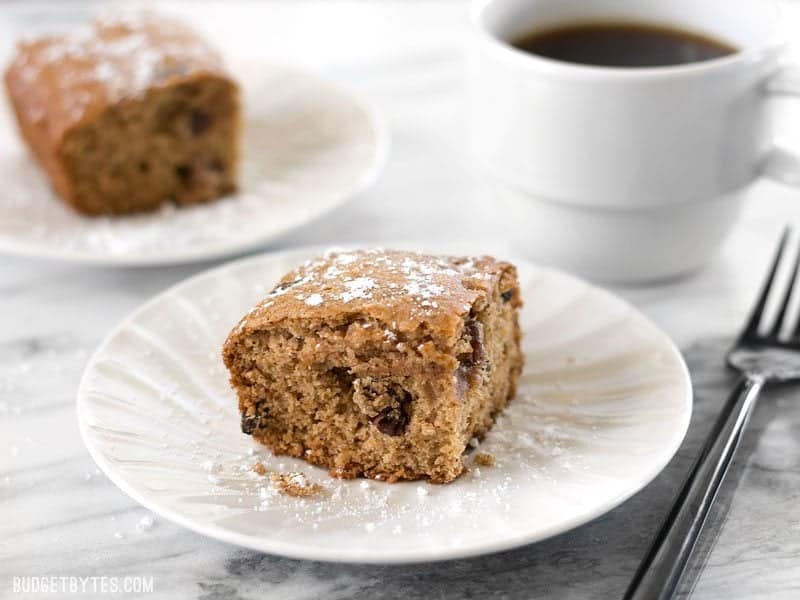 Close up of one slice of Applesauce Cake with a second slice and cup of coffee in the background