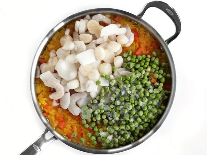 Cooked Rice with Frozen Seafood and Peas added on top in skillet