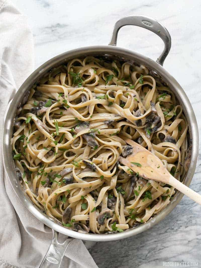 A skillet full of Creamy Mushroom Herb Pasta garnished with parsley and a wooden pasta fork in the side.