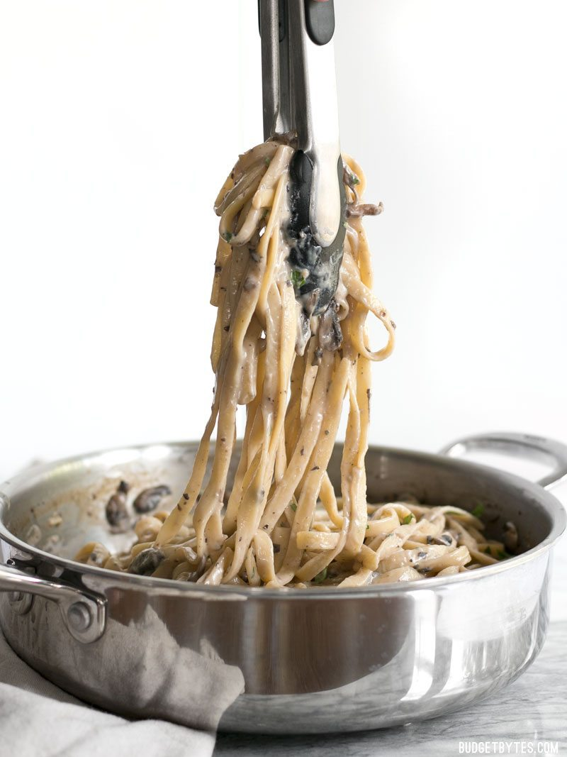 Tongs lifting a bunch of Creamy Mushroom Herb Pasta out of the skillet, viewed from the side.