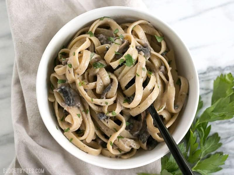 Overhead of Creamy Mushroom Herb Pasta in a bowl with the pasta twirled around a black fork, parsley on the side