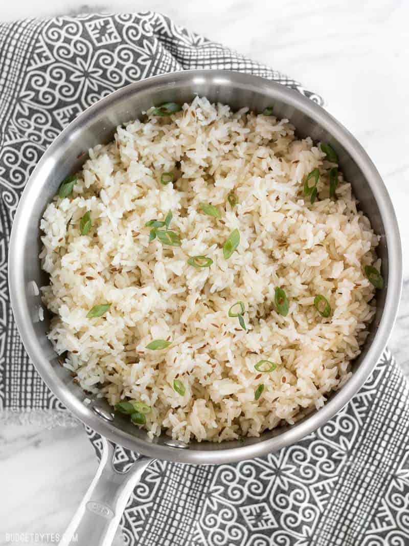 A pot of cumin rice garnished with sliced green onion, sitting on a patterned napkin.