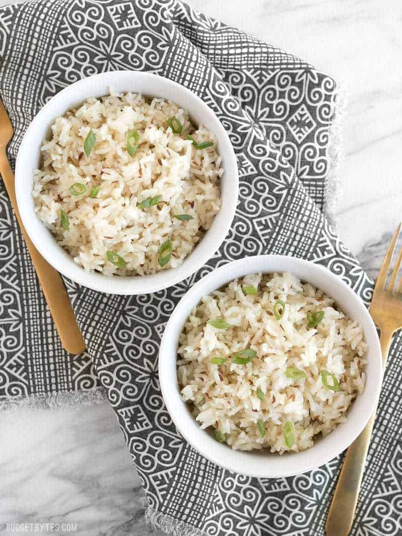 Overhead view of two bowls of cumin rice, garnished with green onion, sitting on a patterned napkin, two gold forks on the sides.