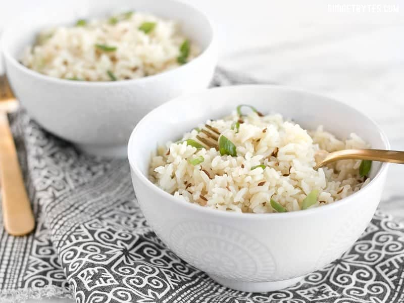 Two bowls of cumin rice, garnished with green onion, and two gold forks.