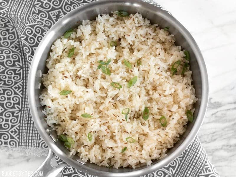 Cumin rice in a sauce pot garnished with sliced green onion sitting on a black and white patterned napkin.
