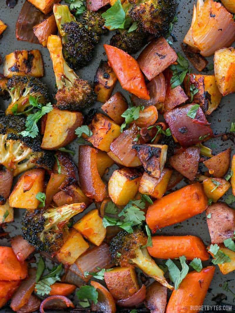 Close up of Harissa Roasted Vegetables garnished with cilantro on a sheet pan.