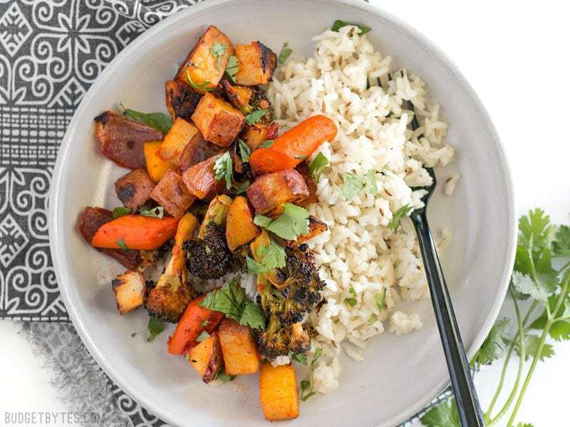 Harissa Roasted Vegetables in a bowl with cumin rice, garnished with cilantro