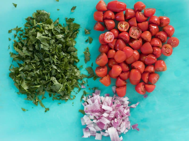 Chopped Parsley, Halved Tomatoes, Diced Onion on a cutting board