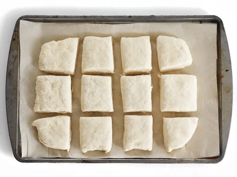 Raw biscuit dough on a parchment lined baking sheet, ready to freeze