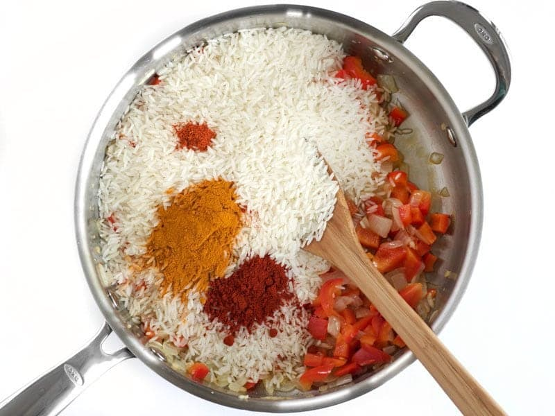 Rice and Spices added to skillet with bell pepper and onion