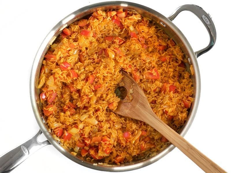Stirred Rice and Spices in skillet with wooden spoon