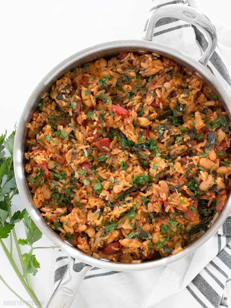 A deep skillet full of Tomato Herb Rice with White Beans and Spinach, garnished with chopped parsley