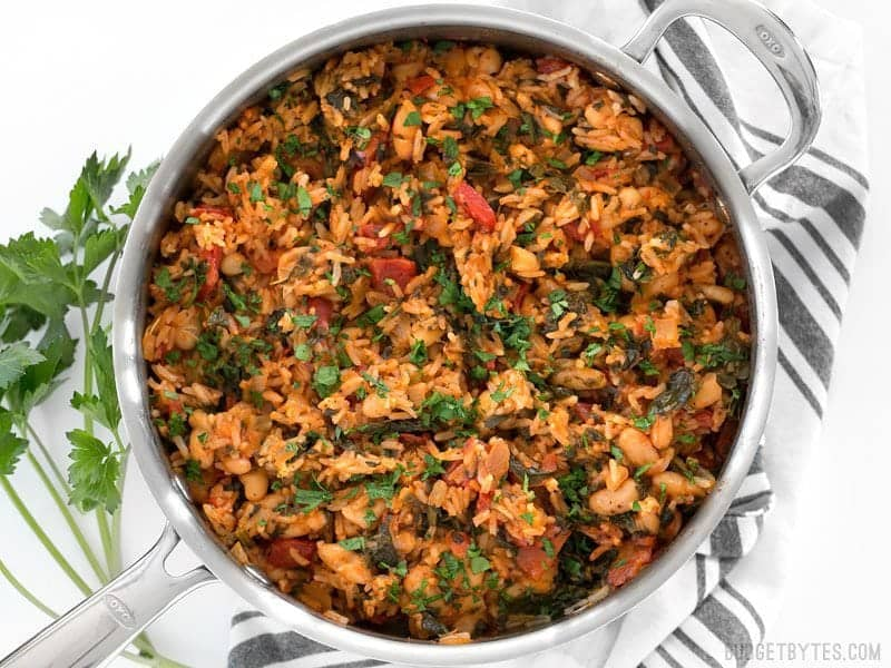 Finished Tomato Herb Rice with White Beans and Spinach in the skillet on a striped napkin