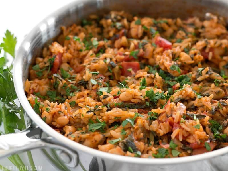 Side view of Tomato Herb Rice with White Beans and Spinach in the skillet