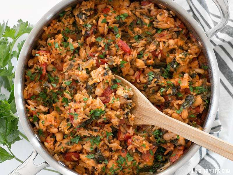 Overhead view of Tomato Herb Rice with White Beans and Spinach being scooped out of the skillet with a wooden spoon.