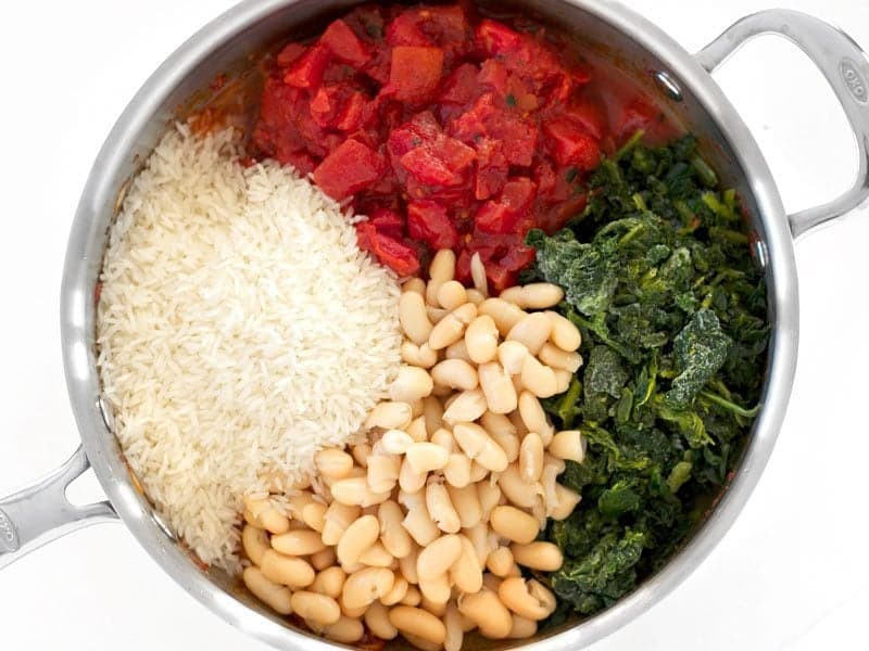 Tomatoes Spinach White Beans and Rice added to the skillet