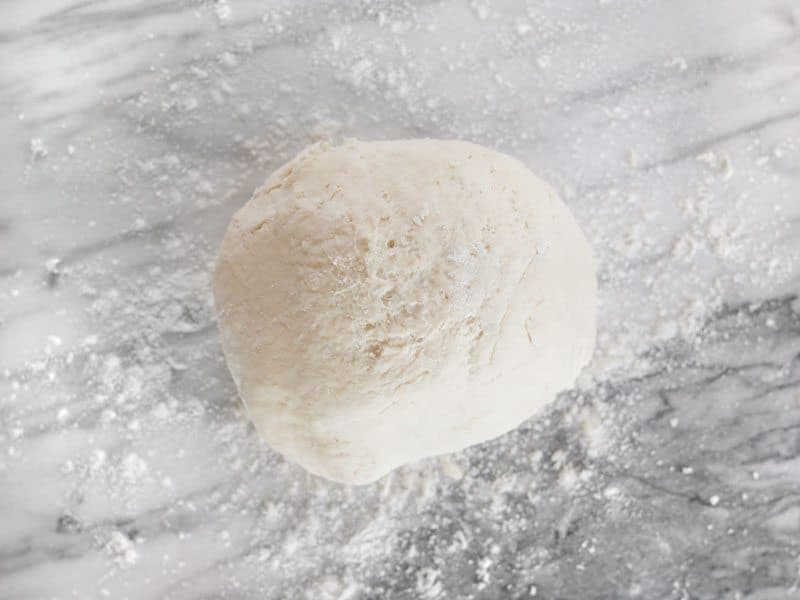 Cohesive Biscuit Dough in a ball on a floured marble surface