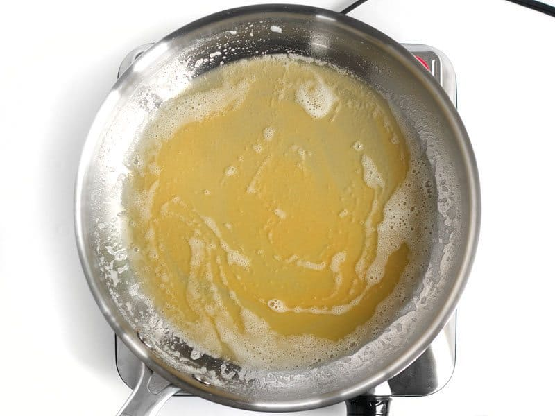 Golden brown butter solids in the skillet full of melted butter, foam is subsiding.