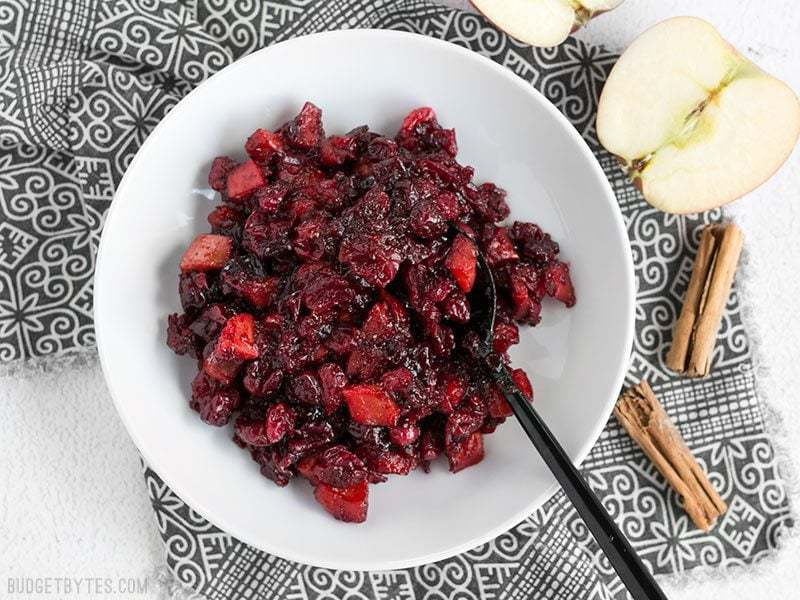 A bowl of thick Roasted Apple Cranberry Relish with a black spoon dug in, cinnamon sticks and apples on the side.