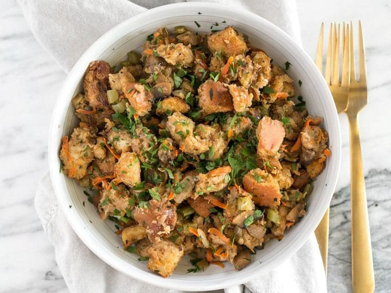 Savory Vegetable Stuffing in a bowl with a gold fork on the side