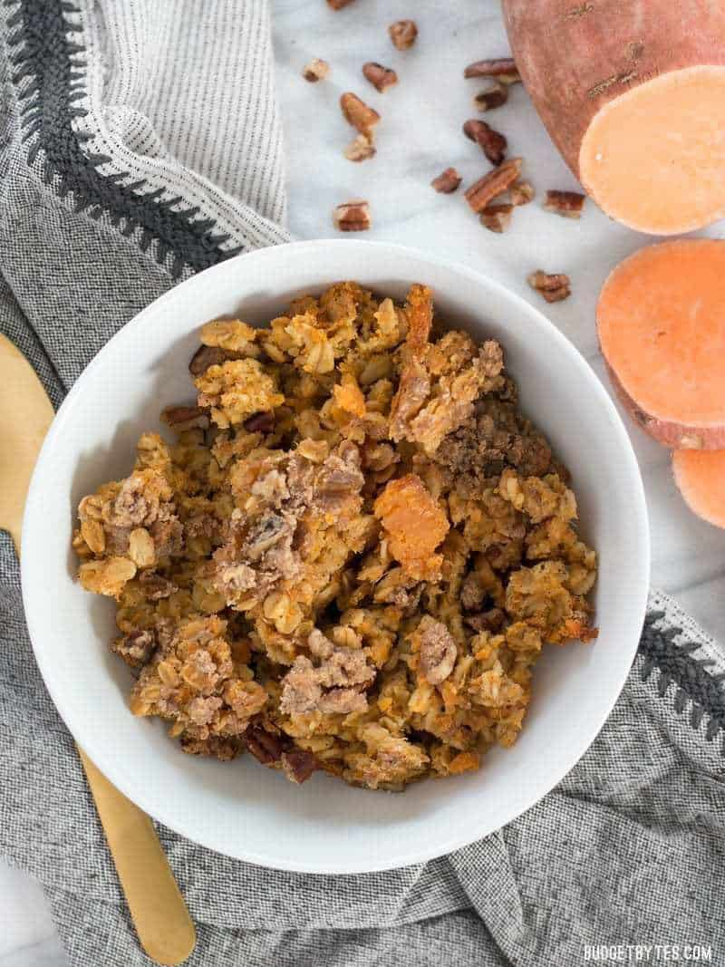 A bowl full of Sweet Potato Casserole Baked Oatmeal with a sliced fresh sweet potato on the side.