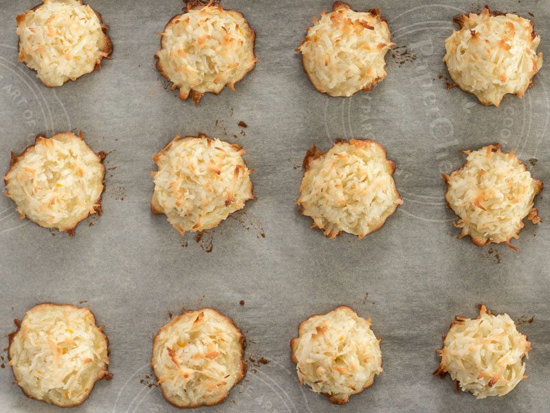 Baked Macaroons on a parchment lined baking sheet, viewed from above