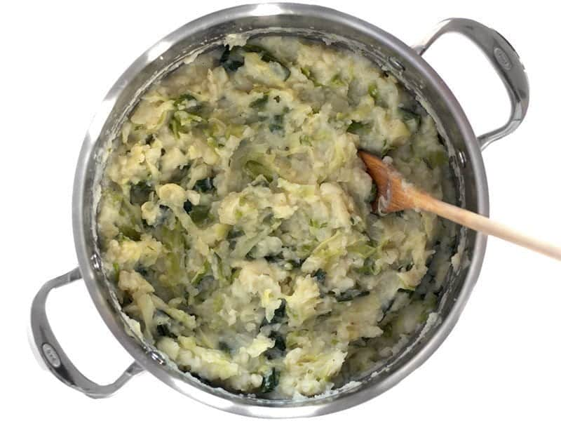 Mashed Colcannon in the stock pot with a wooden spoon