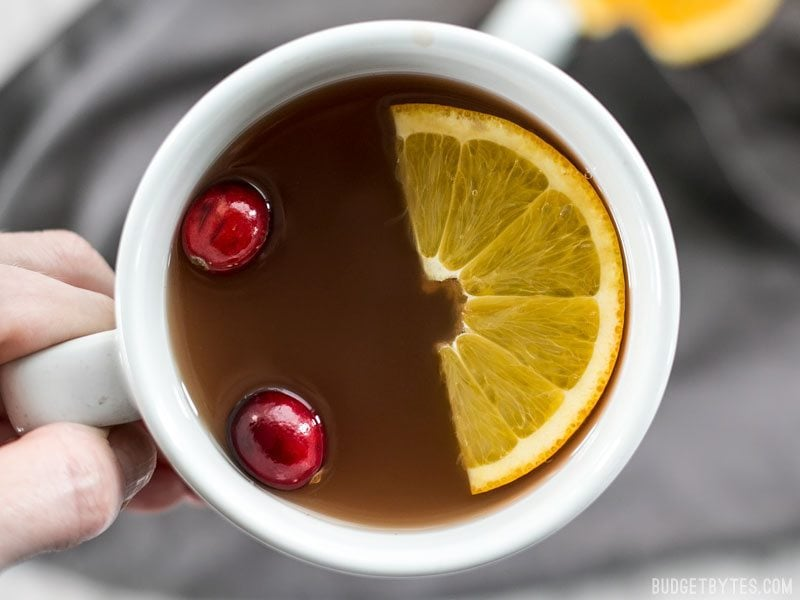 Close up of a mug full of Slow Cooker Spiced Cranberry Apple Cider with cranberries and an orange slice floating on top