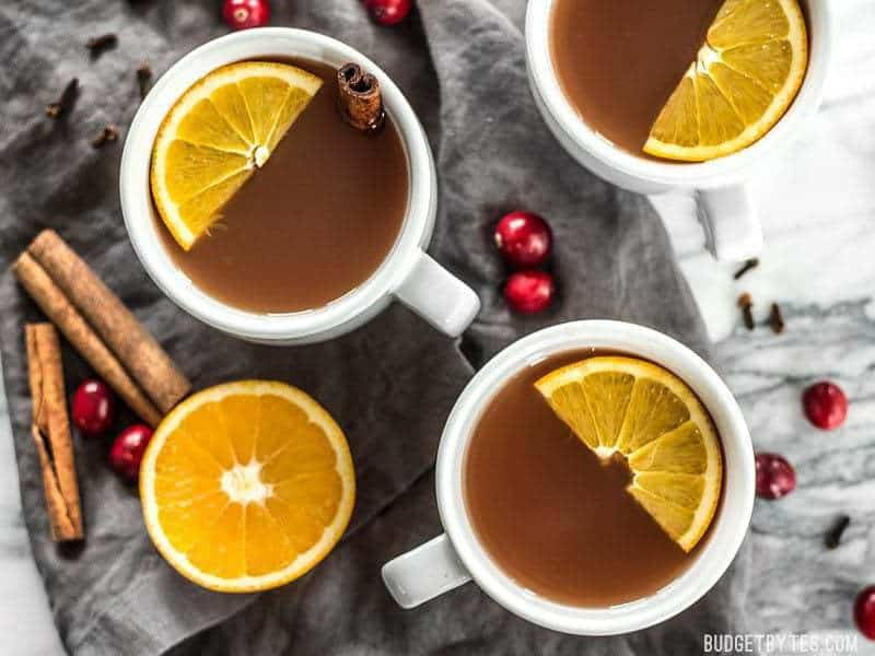 Three mugs of Slow Cooker Spiced Cranberry Apple Cider with garnishes, viewed from above